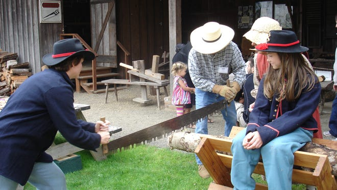 Volunteers demonstrate the long saw at the Old Aurora Colony Historical Museum's Stauff-erWill Farm Living History Program.