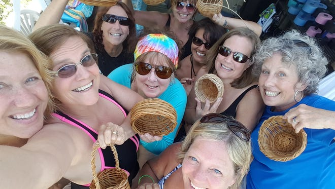 Menopause Camp members pose with partially completed baskets, one of their first group art projects. They weaved the baskets in a swimming pool for both fun and utility - the reeds needed soaked in order to begin weaving. From left to right, Angie Doles, Nancy Robertson, Pam Beck, Karen Perrott, Susan Cunningham, Debbie Zanni, Beth Colburn, Lisa Humphrey, and Theresa Hall.