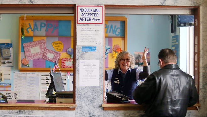 Postal worker Marj Hendershot jokes with a customer Monday at the post office on Pacific Avenue in Bremerton.