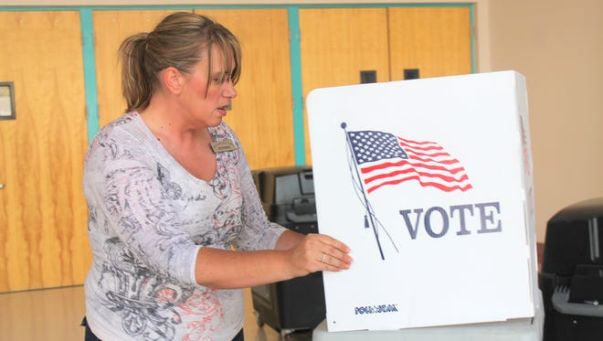 Otero County Deputy Clerk Stephanie Hale sets up a voting booth at the Tays Center, 2235 N. Scenic Drive Monday afternoon.