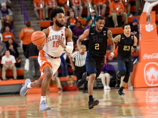 Clemson's Gabe DeVoe, left, brings the ball upcourt pursued by Pittsburgh's Jonathan Milligan (2) and Shamiel Stevenson during the second half of an NCAA college basketball game Thursday, Feb. 8, 2018, in Clemson, S.C. (AP Photo/Richard Shiro)