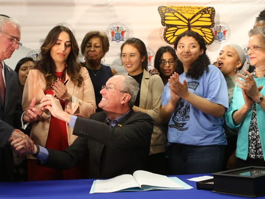 Gov. Phil Murphy gives a pen that he used to sign the bill, to Assemblyman Gary Schaer.  The bill extends financial aid to immigrants who don't have legal status.  It applies to those who reside and go to school in the Garden State. Wednesday, May 9, 2018