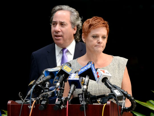 Dianne Grossman, flanked by lawyer Bruce Nagel, speaks