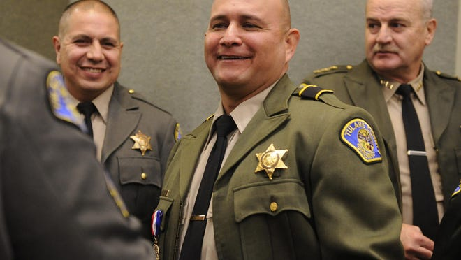 Sgt. Victor Bonilla, left, and Det. Richard Ramirez smile as they are congratulated for being awarded the Medal of Valor. At right is former Undersheriff Robin Skiles.