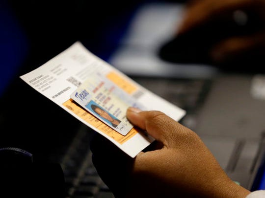 FILE - In this Feb. 26, 2014, file photo, an election official checks a voter's photo identification at an early voting polling site in Austin, Texas. A judge has ruled for a second time that Texas' strict voter ID law was intentionally crafted to discriminate against minorities.