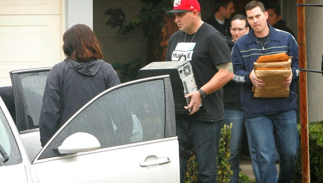 FBI and Homeland Security investigators carry a computer tower and manila envelopes from the Corona, Calif.,  home of Syed Raheel Farook while executing a search warrant at the home on Thursday, Feb. 18, 2016.