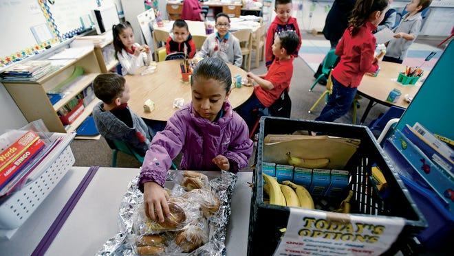 Jayleen Hernandez, 6, gets a bagel for breakfast in her first-grade classroom at Ramirez Thomas Elementary School on Wednesday.
