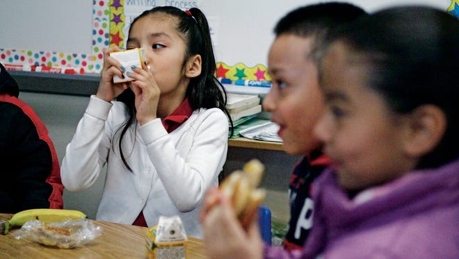 Juliet Cabellero, 7, drinks a carton of juice while having breakfast in her first grade classroom at Ramirez Thomas Elementary School on Wednesday, Feb. 10, 2016. Breakfast after the bell serves about 115,000 kids state-wide breakfast in class after the bell rings to make up for the fact that perhaps they go to school late with no breakfast. Two state senators - Gay Kernan R-Hobbs, and Mimi Stewart, D-Albuquerque, have been taking some heat for trying to change the program to where it can be served before or after the bell to cut down on classroom disruption. But they maintain they don't want to kill the program, which is a pet project of the governor's.