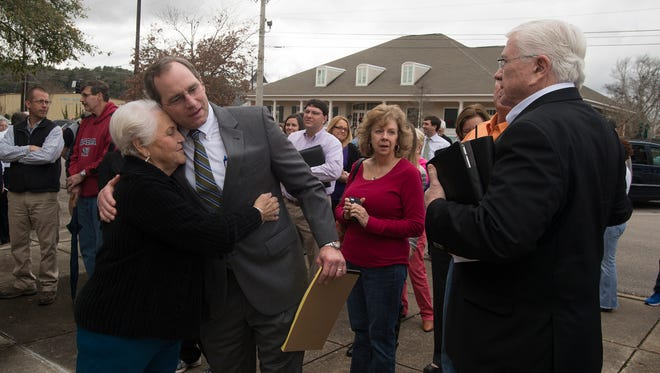 Carol Parker Nunnery embraces Bill Eskridge, a lawyer representing the Historic Prattville Redevelopment Authority, after they won a mortgage foreclosure auction of Daniel Pratt's historic cotton gin factory on Monday, Dec. 29, 2014, outside the Autauga County Courthouse in Prattville, Ala. The property was sold to The Historic Prattville Redevelopment Authority for $1.7 million.