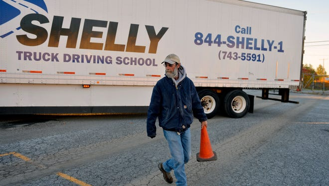 Shelly Truck Driving School manager and lead instructor Jim Burness moves a cone to help mark points for a parallel-parking exercise during an instruction period on Oct. 30 at the school's yard in York City.