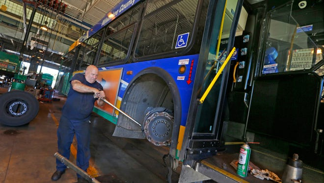 Lee Roller, a Milwaukee County Transit System mechanic, works on replacing a brake caliper on a bus at the fleet maintenance shop.