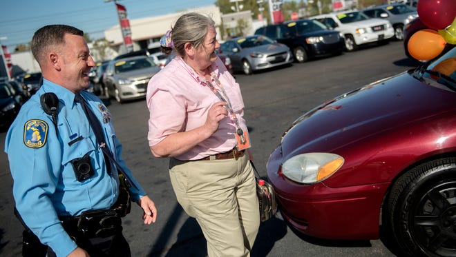 Lansing resident Jo Meade, right, and Lansing Police Officer Trevor Arnold look at Meade's new used car on Tuesday, Oct. 17, 2017, at the Kia of Lansing car dealership. Arnold set up the surprise gifting of the 2007 Ford Taurus to help out Meade who rides her bike to and from work for a total of 16 miles.