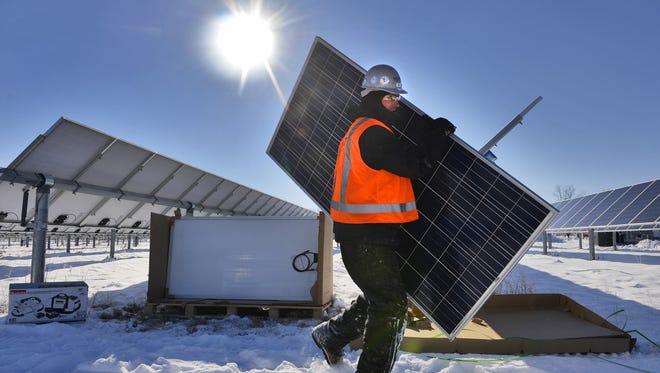 Tim Bode of Hunt Electric, St. Paul, carries a solar panel as he and others work to install an array of 616 new panels in November 2014 at the St. John's Abbey Solar Farm. The new panels are more efficient than existing ones but they will not follow the sun through the sky as the others do.