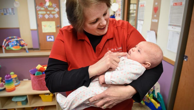 Charla Attarsaheli holds an infant Tuesday, April 10, at Love and Learn Childcare Academy in St. Cloud.