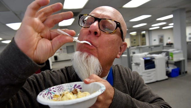 Reporter-News Editor Greg Jaklewicz tries to keep his beard out of his bowl as he savors the flavors of one of the entries in the newspaper's banana pudding contest.