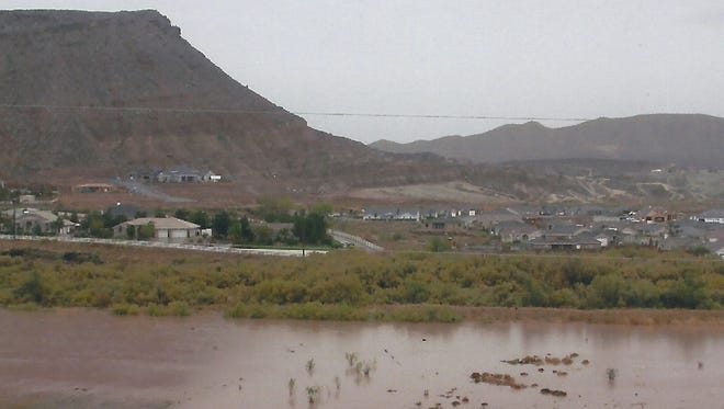 In January of 2005, when flood waters filled the Virgin and Santa Clara Rivers, carrying away homes and washing out bridges, golf courses and roads in Southern Utah, Alice Heaton took the then picture from the back deck of her home on Staheli Hill in Washington. Looking south over what was, at the time, farm fields the Virgin River has spilled over it's banks and filled the flood plain. Just over a decade later, the area has been transformed into one of Washington City's newest parks, the Sullivan Virgin River Soccer Park as can be seen in the now photo taken by Spectrum photographer Jud Burkett.