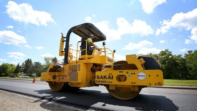 Chris Landon, of Greene, moves a roller machine across freshly laid asphalt on the northbound lanes of Clemens Center Parkway in Elmira Friday, July 24.