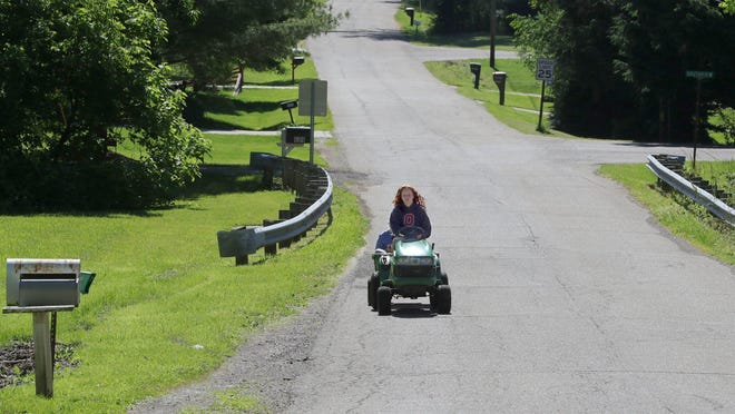 Alison Lantz drives her John Deere tractor on Ott Drive in New Franklin while pulling her friend Madison Prentice on Friday. Neighbors in the area have been feuding over loose cows.