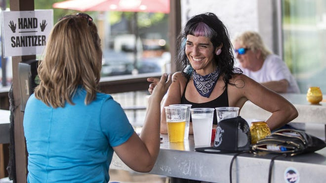 A woman who wants to be known as Kolby Pop, left,  and Sarah Mitchell, right,  enjoy beers at the Crow bar in downtown Austin on May 22, one of the first days of Texas bars reopening.