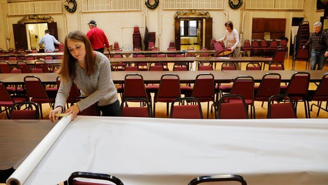 Volunteer Emily Vealey spreads plastic sheeting as a table cloth for the LUM Thanksgiving dinner Wednesday, November 26, 2014, at Central Presbyterian Church, 31 N. 7th Street in downtown Lafayette. the annual community Thanksgiving dinner drew 800 people last year. Officials at the church anticipate serving over 900 people at this year's dinner.