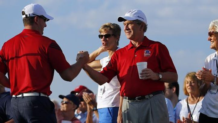 Retired Marine Cpl. Michael Meyer, left, shakes hands with former U.S. President George W. Bush after teeing off in the Bush Center Warrior Open golf tournament during an opening ceremony, Thursday, Oct. 2, 2014, at the Las Colinas Country Club in Irving, Texas. This is the fourth year for the 36-hole tournament featuring servicemen wounded in combat service.