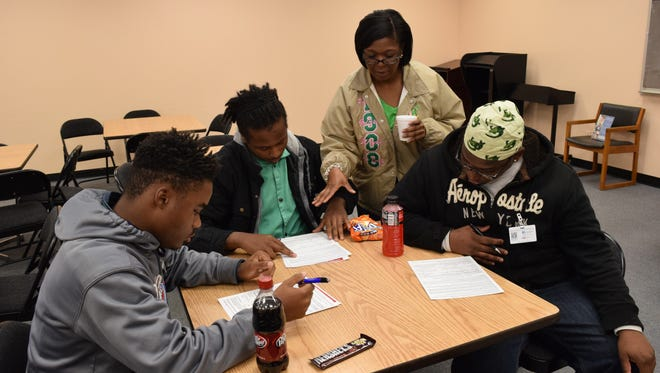 Joan Walker (third from left), a member of Zeta Lambda Omega Chapter of Alpha Kappa Alpha Sorority Inc., instructs Davin Marks (left), Elajuwon Bishop and DeMarcus Fells, welding students at Central Louisiana Technical Community College, on filling out a voter registration form. CLTCC and the sorority chapter held a voter registration drive Thursday in preparation for the upcoming presidential primary election March 5.
