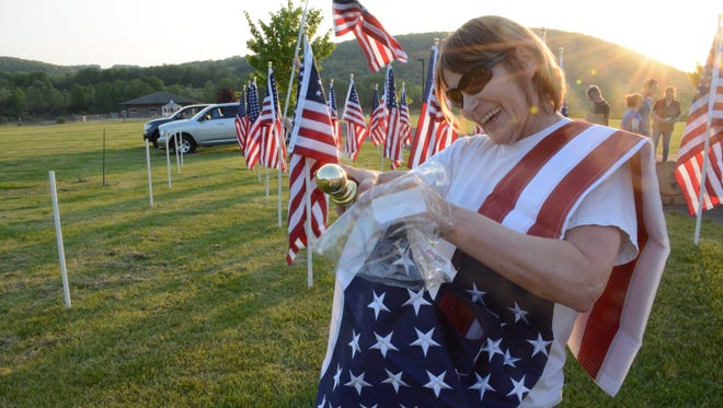 U.S. Air Force Veteran Lisa Houston helps with an American Flag display Wednesday to honor individuals ahead of Memorial Day Monday. The display is also a fundraiser for the Conklin Veterans Memorial. Houstin said her brother is also a veteran and when he was drafted during the Vietnam War, she said she had to go with him.