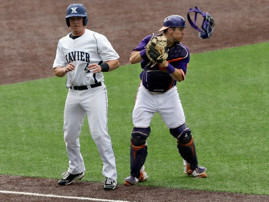 Xavier's Derek Hasenbeck (4) is tagged out by Clemson catcher Chris Okey after Hasenbeck was caught off third base during the sixth inning of an NCAA college baseball regional tournament game Saturday, May 31, 2014, in Nashville, Tenn. (AP Photo/Mark Humphrey)