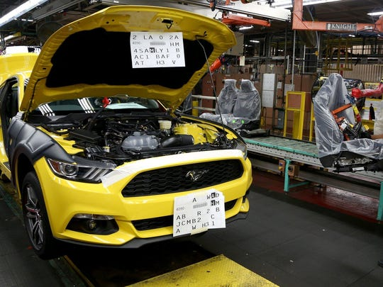 Karla Browen, 41, of Taylor waits for the production line to start up again so she could install the driver's seat inside a 2015 Ford Mustang GT at the Flat Rock plant.