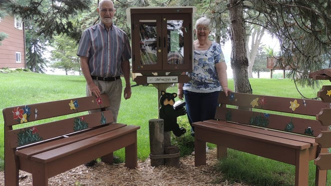 """Bob and Ellen Fisher are shown with the """"Little Free Library"""" that was constructed by  Bob and has been set up in their front yard at N10464 Chief Kuno Trail in the town of  Fox Lake. The shady spot includes two benches to encourage visitors to sit and relax while selecting a book."""