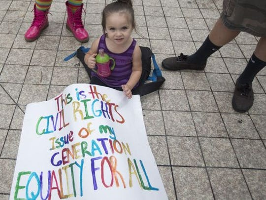 In this July 2, 2014 photo, an unidentified child of a same-sex couple sits next to a protest sign during a court hearing on gay marriage in Miami.