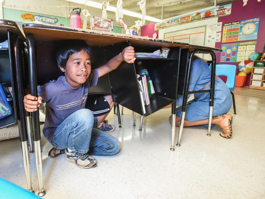 Student Burnett Marunu braces himself underneath his desk as he, fellow second-graders and his teacher, Charity Catunao, participates in the annual Great Guam ShakeOut earthquake drill at Agana Heights Elementary School on Thursday, Oct. 20.