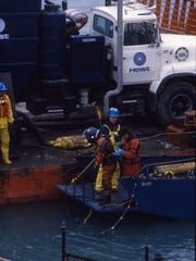A diver suits up alongside vacuum trucks loaded onto barges on the St. Clair River in November 1985 during the cleanup of a blob of chemicals in the river.