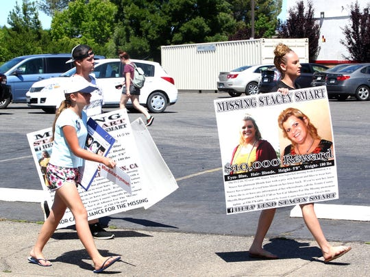 Nicole Santos -Hamann, right, holds a poster with information on her mother's disappearance.