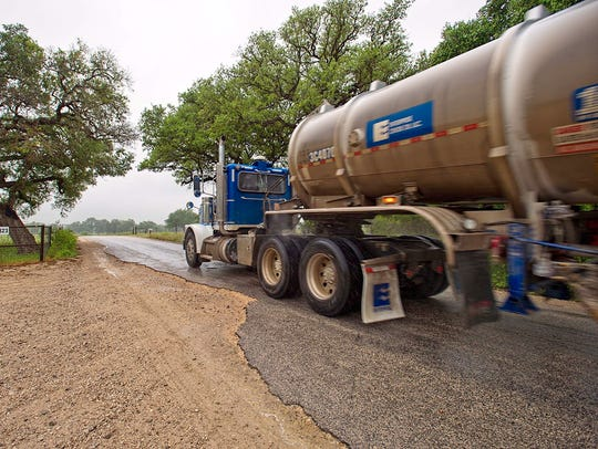 Trucks travel along FM 2067 near Cheapside on April