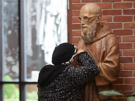 Kaukab Denha, Troy, 59 prays at the Solanus Casey Center in Detroit after Pope Francis announced the beatification of Father Solanus Casey.