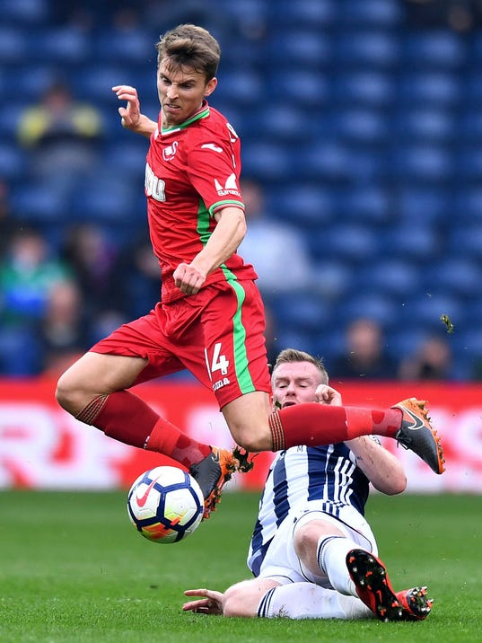 Swansea City's Tom Carroll avoids a challenge from West Bromwich Albion's Chris Brunt during their English Premier League soccer match between West Bromwich Albion and Swansea City at the Hawthorns, West Bromwich, England. Saturday, April 7, 2018. (Anthony Devlin/PA via AP)