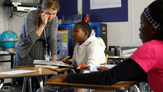 Hilary Haskell, a teacher of the English Language Learner class, helps Gaetan NDekezi with his classwork at Appleton North High School on Tuesday.