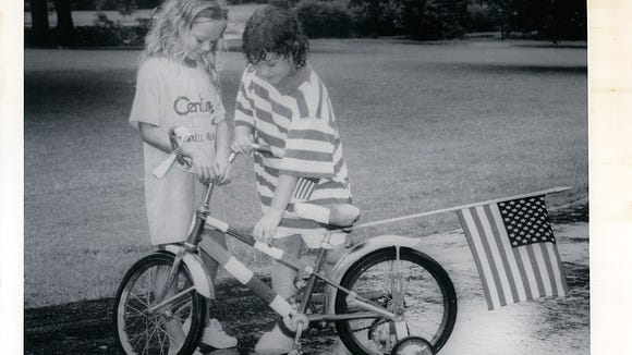 Amanda Cox (left), 7, and Kate Johnson, 7, decorate a bike with an American Flag at the Meadowere Parade on July 4th of 1987.