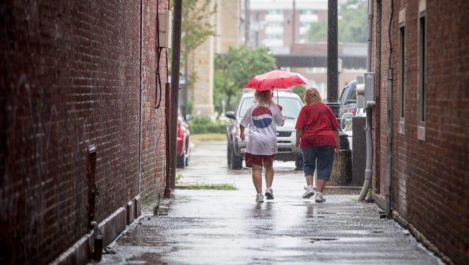 Umbrella wielding pedestrians make their way through downtown Muncie during some moderate rainfall.