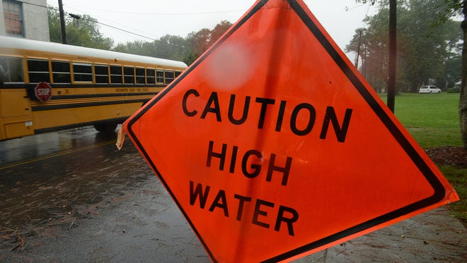 A Northampton school bus passes a warnignn sign in Cheriton, Va. on Tuesday, Sept. 9, 2014. Northampton County Public Schools delayed school openings for two hours on Tuesday due to coastal flooding and heavy rain.