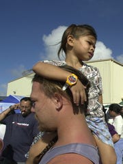 In this Dec. 17, 2002 file photo, Kameron Emerson, 4, of Harmon sits on his father William Emerson's shoulder while waiting in line at the American Red Cross Service Center at Astumbo Gym following Supertyphoon Pongsona.