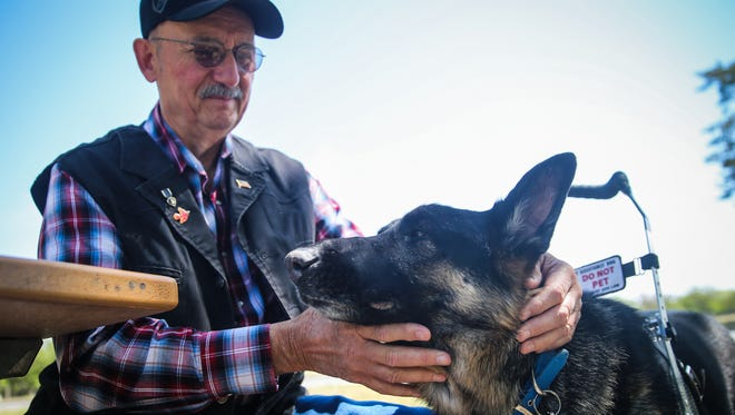 Phillip Dowsett pets Rex, his German Shepherd service dog, Tuesday, April 17, 2018, by the Concho River. Dowsett is a Vietnam veteran and authored 'And The Red Bird Sings.'