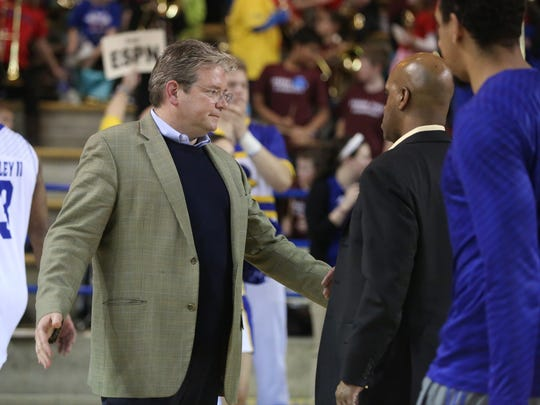 Interim Delaware athletic director Matt Robinson (left) greets men's basketball players and coaches, including now-deposed head coach Monte Ross, after Delaware's 94-79 loss to William and Mary at the Bob Carpenter Center in January.