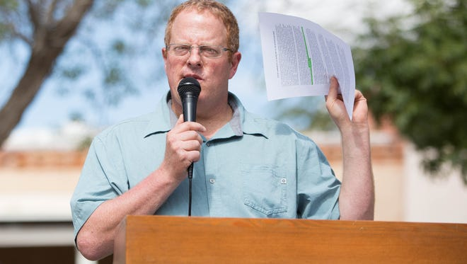 Jeff Steinborn, New Mexico State Representative, holds up a summary of Interior Secretary Ryan Zinke's report Thursday Aug 24, 2017, about the Organ Mountains-Desert Peaks National Monument. Zinke filed the report with the Trump Administration, but it was not made public. Steinborn, along with other local officials, held a news conference at the Plaza de Mesilla, where they addressed the summary.