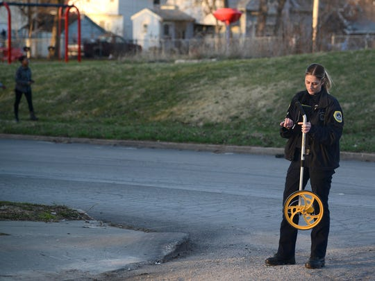 A Des Moines police officer investigates a shooting