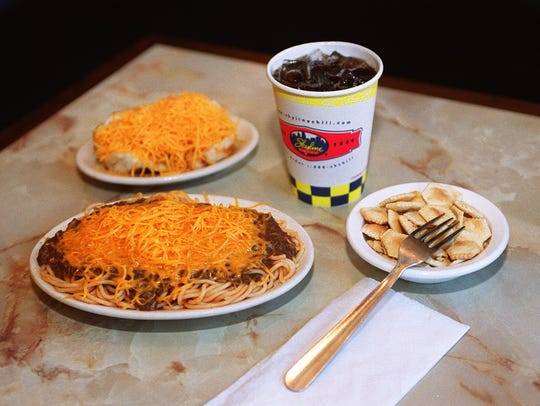 A table is set with a Skyline Chili cheese coney and chili spaghetti meal.