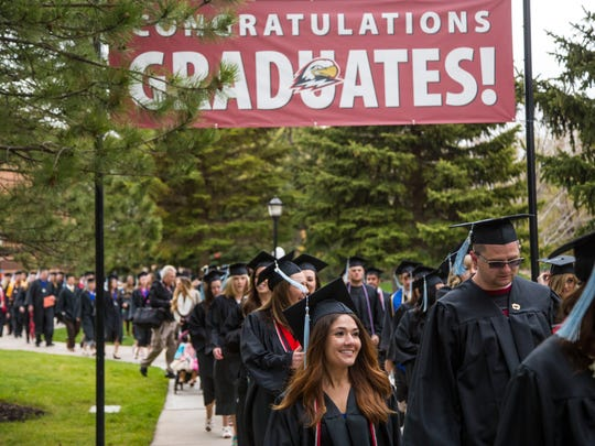 Graduates march from the clock tower to the Centrum