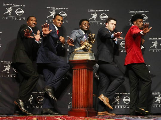 Dede Mayfield of Oklahoma, Deshaun Watson of Clemson, Jabrill Peppers of Michigan (center), Baker Mayfield of Oklahoma and Lamar Jackson of Louisville showing off their Heisman pose in front of the trophy during the pre-ceremony news conference in December.
