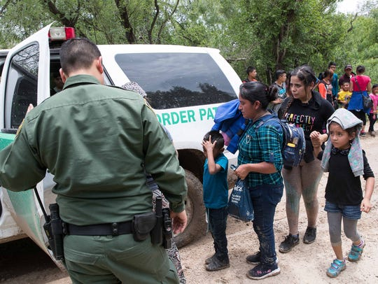 Border Patrol agents take a group of migrant families